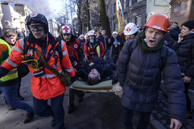 An Interior Ministry member, who was injured during clashes with anti-government protesters, is transported on a stretcher in Kiev. (Photo by Andrew Kravchenko/Reuters)