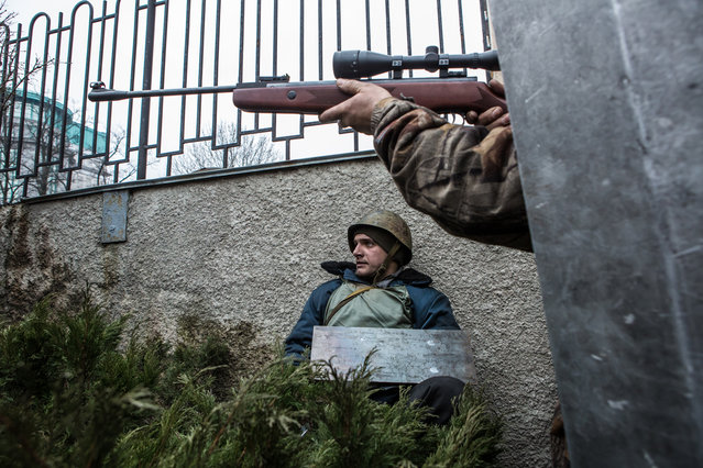 An anti-government protester aims a gun in the direction of suspected sniper fire near the Hotel Ukraine, on February 20, 2014. (Photo by Brendan Hoffman/Getty Images)