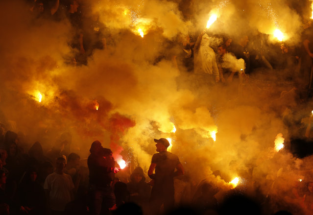 Partizan soccer fans light torches during a Serbian National soccer league derby match between Red Star and Partizan, in Belgrade, Serbia, Saturday, April 25, 2015. (Photo by Darko Vojinovic/AP Photo)