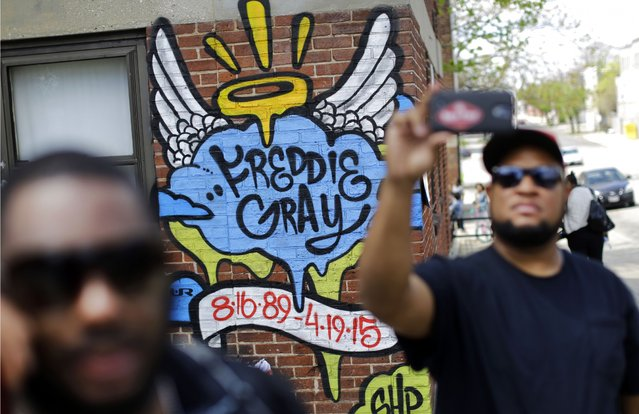 J.R. White, right, takes a selfie in front of a mural that was painted at the site of Freddie Gray's arrest, Saturday, May 2, 2015, in Baltimore, as protesters prepare to march to City Hall. (Photo by Patrick Semansky/AP Photo)