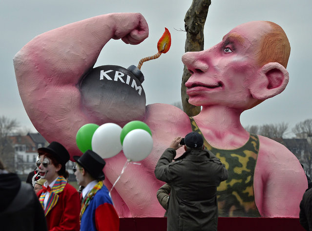 """A man takes pictures of a carnival float depicting  Russia's president Vladimir Putin  showing his muscles and a bomb reading """"Crimea"""", prior to the traditional carnival parade in Duesseldorf, western Germany, on Monday, March 3, 2014. The foolish street spectacles in the carnival centers of Duesseldorf, Mainz and Cologne, watched by hundreds of thousands of people, are the highlights in Germany's carnival season on Rosemonday. (Photo by Martin Meissner/AP Photo)"""