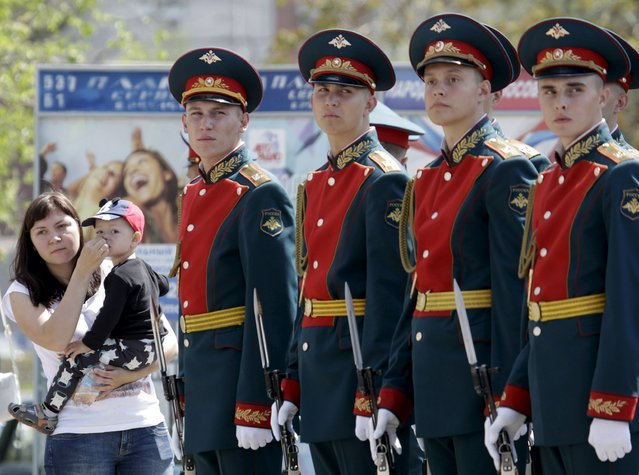 A woman holds a child while standing near honour guards during the so-called parade of children's troops in Rostov-on-Don, southern Russia, May 14, 2015. (Photo by Eduard Korniyenko/Reuters)