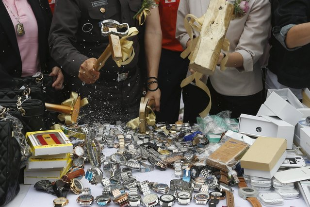 Officials from Thailand's Department of Intellectual Property and police force destroy counterfeit goods in Pathum Thani province, on the outskirts of Bangkok, Thailand March 31, 2016. (Photo by Chaiwat Subprasom/Reuters)