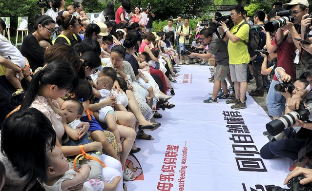 People take pictures and video as women breastfeed their children during an event to promote breast feeding in Fuzhou, Fujian province, China, May 16, 2015. According to local media, over 80 mothers participated in the event on Saturday. (Photo by Reuters/Stringer)