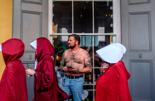 Handsmaid themed protesters march down the French Quarter of New Orleans, Louisiana, on May 25, 2019, to protest the proposed Heartbeat Bill that will ban abortion after 6 weeks in that state, scheduled for a vote on May 28. (Photo by Emily Kask/AFP Photo)