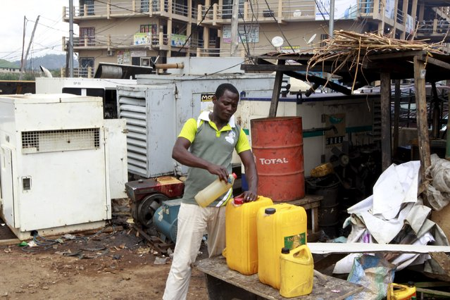 A man seen pouring diesel into a container next to power generators at the Area 10 shopping centre in Abuja, Nigeria May 25, 2015. (Photo by Afolabi Sotunde/Reuters)