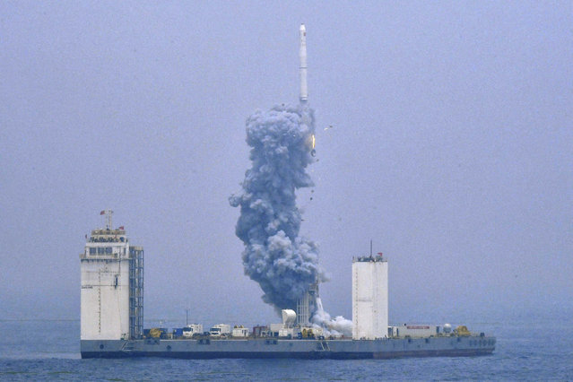 In this photo released by Xinhua News Agency, a Long March-11 solid propellant carrier rocket blasts off from a mobile launch platform in the Yellow Sea off east China's Shandong Province, Wednesday, June 5, 2019. China has for the first time launched a rocket from a mobile platform in the Yellow Sea, sending a five commercial satellites and two others containing experimental technology into space. (Photo by Zhu Zheng/Xinhua via AP Photo)