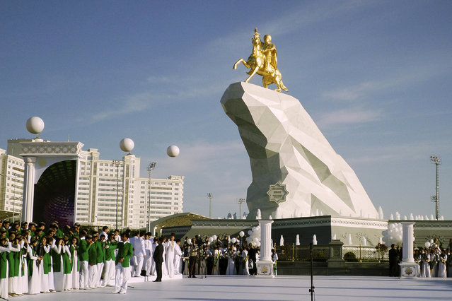 People gather for the monument unveiling ceremony in Ashgabat, Turkmenistan Monday, May 25, 2015. The isolated energy-rich Central Asian nation of Turkmenistan has unveiled a gold-leafed statue of the president in a gesture intended to burnish the leader's burgeoning cult of personality. (Photo by Alexander Vershinin/AP Photo)