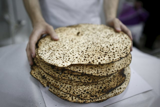 An ultra-Orthodox Jewish wraps fresh matza, traditional unleavened bread eaten during the upcoming Jewish holiday of Passover, in the southern city of Ashdod April 17, 2016. (Photo by Amir Cohen/Reuters)