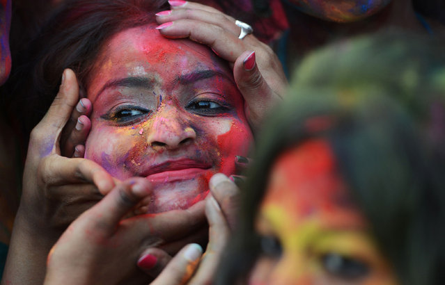 Indian students smear coloured powder at an event to celebrate the Hindu festival of Holi in Kolkata on March 7, 2017. Holi, the popular Hindu spring festival of colours is observed in India at the end of the winter season on the last full moon of the lunar month, and will be celebrated on March 13 this year. (Photo by Dibyangshu Sarkar/AFP Photo)
