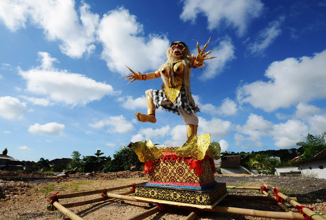 "An effigy known as ""Ogoh-ogoh"" symbolising evil is displayed in a field in the residential area in Jimbaran district as the Indonesian holiday island shut down for a day of silence to mark Nyepi, the Hindu new year on March 31, 2014. Retailers closed their shops and many tourists stayed inside their hotels for a day of reflection that is supposed to be free from daily routine, including work and play. Guards with sticks and traditional daggers enforced the public observance among the Hindu- majority population. (Photo by Sonny Tumbelaka/AFP Photo)"