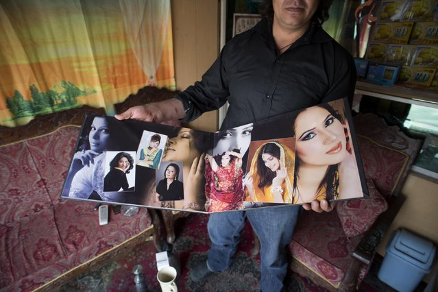 A wedding photographer shows bridal portraits at his photo studio in Kabul March 6, 2014. (Photo by Morteza Nikoubazl/Reuters)