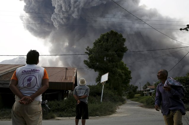 Residents look on as ash spews from Mount Sinabung volcano during an eruption as seen from Kuta Tengah village in Karo Regency, North Sumatra province, Indonesia June 28, 2015. More than 10,000 people from 12 villages, who are living around the slopes of Mount Sinabung, left their homes and moved to refugee camps, local media reported. (Photo by Reuters/Beawiharta)