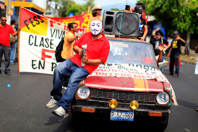 A masked demonstrator rides in a car during the May Day march in San Salvador, El Salvador May 1, 2016. (Photo by Jose Cabezas/Reuters)
