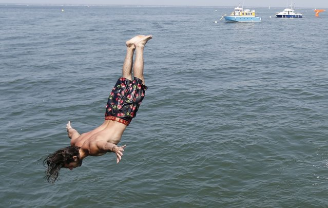 A man dives from a jetty into the Bassin d'Arcachon Sea during a warm and sunny day in Arcachon near Bordeaux, southwestern France, July 1, 2015. (Photo by Regis Duvignau/Reuters)