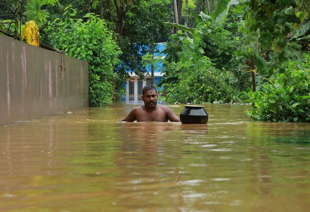 A man walks in flood waters at Eloor area in Ernakulam district, in the south Indian state of Kerala, on August 9, 2019. Floods that have killed more than 20 people forced the closure of Kochi international airport on August 9 as the south Indian state of Kerala confronted a second straight year of crisis level downpours. (Photo by AFP Photo/Stringer)