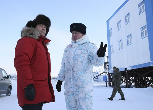 Russian Prime Minister Dmitry Medvedev, left, listens to an officer as he visits Franz Josef Land archipelago in Arctic Russia, Wednesday, March 29, 2017. (Photo by Yekaterina Shtukina/Pool Photo via AP Photo)