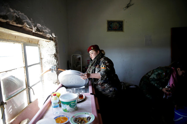 Iraqi Kurdish female fighter Haseba Nauzad, 24, washes a tray in a kitchen at a site near the frontline of the fight against Islamic State militants in Nawaran near Mosul, Iraq, April 20, 2016. (Photo by Ahmed Jadallah/Reuters)