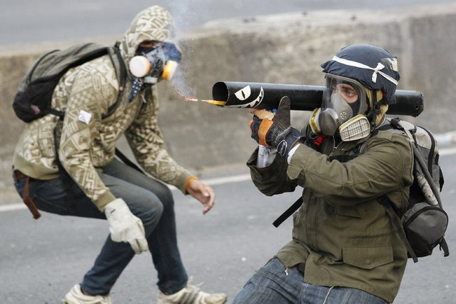 An anti-government protester fires a homemade mortar toward police officers during a demonstration in which masked youths battled police and blocked a main highway in Caracas, Venezuela, on April 21, 2014. Protests against the government of President Nicolas Maduro have led to violence that has killed at least 41 people since early February, according to official figures. (Photo by hristian Veron/Reuters)