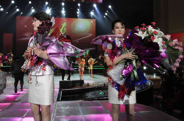 In this Friday, March 28, 2014 photo, singers of the Moranbong Band hold bouquets of flowers during their performance in Pyongyang, North Korea. Step aside, Sea of Blood Opera. North Korean leader Kim Jong Un's favorite guitar-slinging, miniskirt-sporting girl group, the Moranbong Band, is back. And these ladies know how to shimmy. (Photo by Jon Chol Jin/AP Photo)