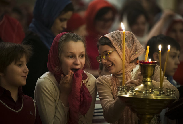 Girls react during the Orthodox Easter service at the Church of the Holy Martyr Tatiana just next to the Kremlin Wall in Moscow, Russia, Sunday, April 16, 2017. (Photo by Alexander Zemlianichenko/AP Photo)