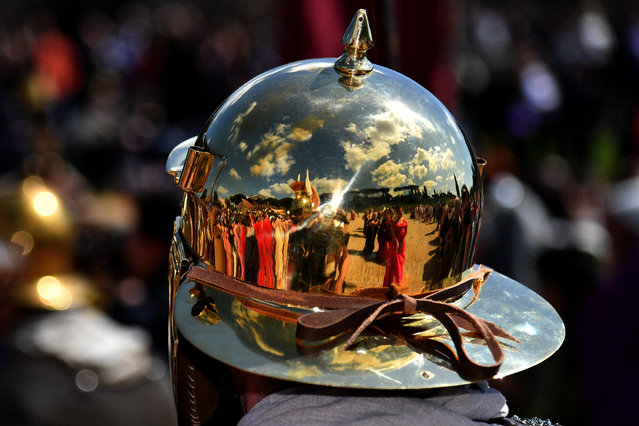 People dressed as ancient Roman reflect on a helmet during a parade to mark the anniversary of the foundation of Rome in 753 BC, on April 23, 2017 in Rome, Italy. (Photo by Alberto Pizzoli/AFP Photo)