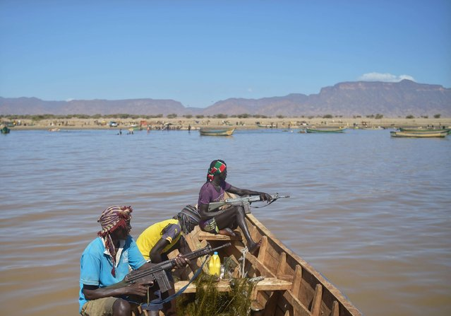 Armed fishermen from Kenya's Turkana county return from a fishing expedition aboard a boat on March 24, 2017 near Lowarengak, on the western shores of Lake Turkana, northern Kenya. Lake Turkana has gradually receded in recent years leading to diminished fish stocks and territory that has forced traditional communities on the eastern as well as the northern shores, in Ethiopia, of the world's largest permanent desert lake within undesired proximity of each other regularly ending in deadly clashes. (Photo by Tony Karumba/AFP Photo)