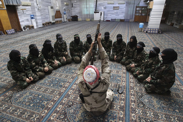 Abu al-Taib, the leader of Ahbab Al-Mustafa Battalion, demonstrates to female members as he holds a gun during a military training in a mosque in the Seif El Dawla neighbourhood in Aleppo June 24, 2013. (Photo by Muzaffar Salman/Reuters)