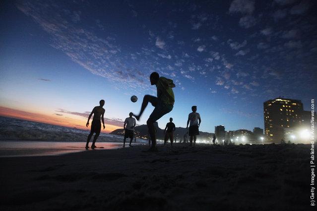 Brazilian revelers play soccer at sunset during Carnival celebrations along Ipanema beach