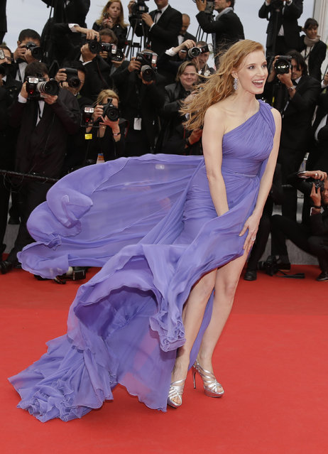 Actress Jessica Chastain holds down her dress as she poses for photographers as she arrives for the screening of Foxcatcher at the 67th international film festival, Cannes, southern France, Monday, May 19, 2014. (Photo by Thibault Camus/AP Photo)
