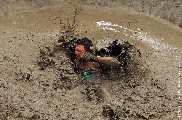 Predag Trajkvoc falls in the mud after swinging across the Piranha Pit as he competes in The Tough Bloke Challenge