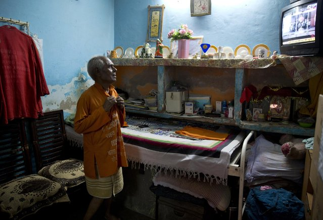 """In this June 8, 2015 photo, Omkarnath, who goes by the name """"Medicine Baba"""", puts on his customary saffron colored tunic as he gets ready for the day at his rented accommodation at a fetid slum in New Delhi, India. (Photo by Saurabh Das/AP Photo)"""