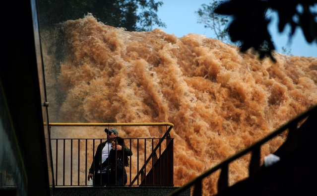 A couple stands on a bridge at the Iguacu Falls on June 12, 2014, in Foz do Iguacu, Brazil, following the overflowing of the Parana river. In neighbouring Paraguay flooding has forced the evacuation of about 150,000 people in Paraguay's capital city Asuncion, authorities said. (Photo by Norberto Duarte/AFP Photo)