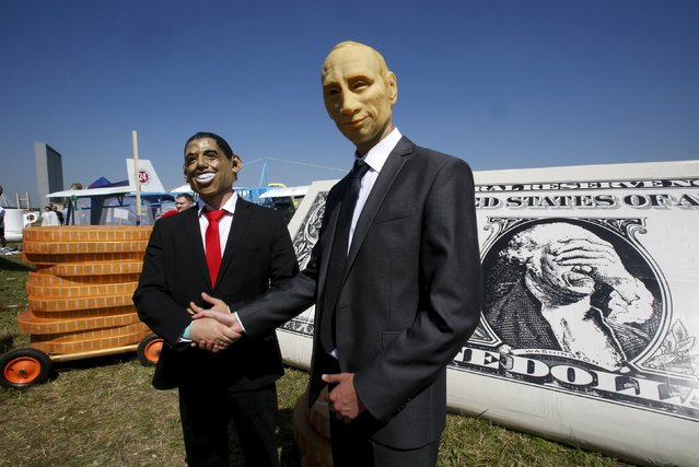 Participants, wearing masks of Russian President Vladimir Putin (R) and U.S. President Barack Obama, pose for a picture during preparations before the Red Bull Flugtag Russia 2015 competition in Moscow, Russia, July 26, 2015. (Photo by Sergei Karpukhin/Reuters)