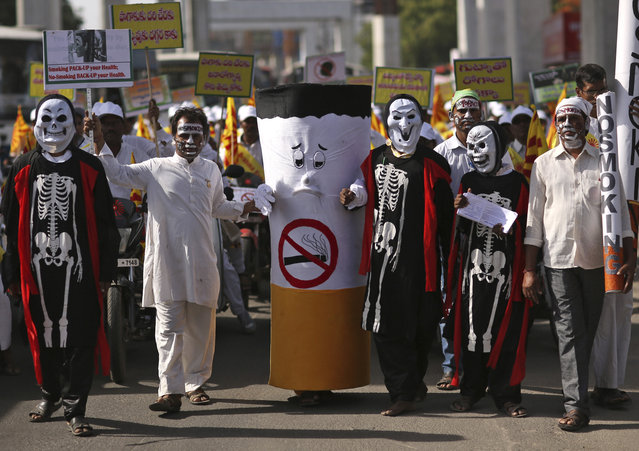 Indians dressed as skeletons and cigarette in a rally to mark World No Tobacco Day in in Hyderabad, India, Tuesday, May 31, 2016. The member states of the World Health Organization observe May 31 every year as World No Tobacco Day to draw global attention to the tobacco epidemic and to the preventable death and disease it causes. (Photo by Mahesh Kumar A./AP Photo)