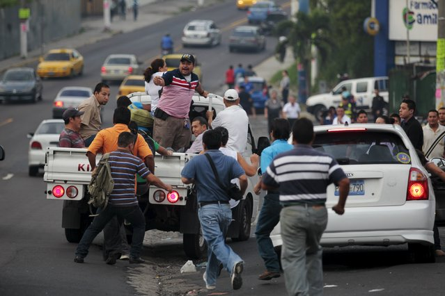 People run to ride in the back of a pick up truck during the second day of a suspension of public transport services in Mejicanos, El Salvador July 28, 2015. (Photo by Jose Cabezas/Reuters)