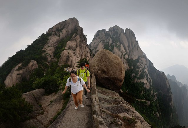 This photo taken on June 16, 2014 shows Chinese tourists hiking on Lotus Peak which is the most revered of the Huangshan (Yellow Mountains) peaks at the park in Anhui Province. The UNESCO World Heritage Site is one of China's major tourist destinations and has been a source of inspiration to Chinese painters, writers and poets for thousands of years. (Photo by Mark Ralston/AFP Photo)