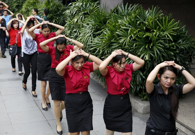 Employees take part in an earthquake drill in Manila's financial district in Makati city, Metro Manila July 30, 2015. Hundreds of thousands of Filipinos on Thursday rushed out from shopping malls, office towers, and public buildings to open spaces across the Philippine capital in a simulated earthquake drill, media reports said. (Photo by Erik De Castro/Reuters)