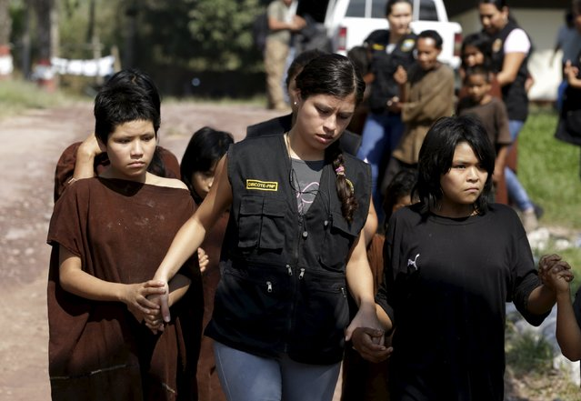 Peruvian anti-terrorist forces escort a group of rescued people from Shining Path rebels at Mazamari military base in the Amazon province of Satipo, Peru, August 1, 2015. Peruvian special forces rescued another 7 children and 8 men and women on Friday, some of whom had been raped and held captive for three decades, when they made another raid in a southeastern jungle camp of the left-wing Shining Path rebel group. (Photo by Mariana Bazo/Reuters)
