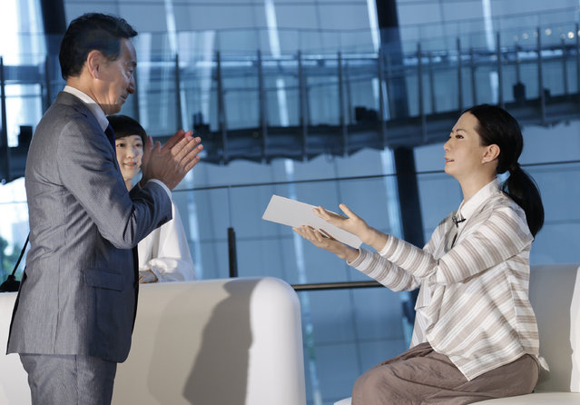 National Museum of Emerging Science and Innovation Miraikan Chief Executive Director Mamoru Mohri hands a female-announcer robot called Otonaroid a letter of appointment to assign as a guide at the museum as a girl robot called Kodomoroid, second left, looks on during a press event in Tokyo Tuesday, June 24, 2014. The latest creations from Japanese android expert Hiroshi Ishiguro are Otonaroid, Kodomoroid and Telenoid, a hairless mannequin head with pointed arms that serves as a cuddly companion. (Photo by Shizuo Kambayashi/AP Photo)