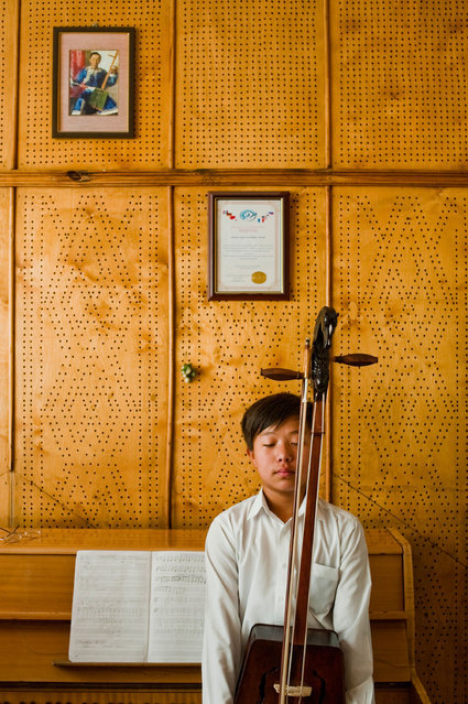 """Morin Khuur Student"". The Morin Khuur (the Horsehead Fiddle) is the national instrument of Mongolia. Its creation is poetically described in the legends of Mongolia. The sound created is of the horse, the loved and respected animal sacred to all Mongolians. I went to meet with the head of the Morin Khuur department at the Music College in the capital whilst visiting Mongolia. Stepping into his office this student was diligently playing. Photo location: Ulaanbaater, Mongolia. (Photo and caption by Sophie Howarth/National Geographic Photo Contest)"