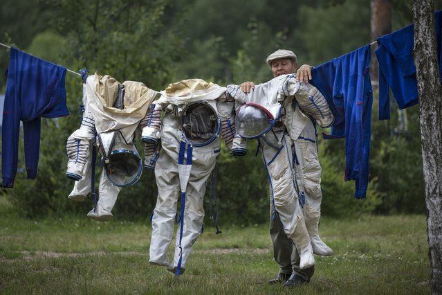 An employe of Russian Space Training Center hangs out to dry space suits of Russian cosmonaut Anatoly Ivanishin, NASA's U.S. flight engineer Kathleen Rubins, and Japanese space agency's flight engineer Takuya Onishi, right, after their undergoing  training near in Noginsk, 60 km (38 miles) east of Moscow, Russia, Wednesday, July 2, 2014. (Photo by Alexander Zemlianichenko/AP Photo)