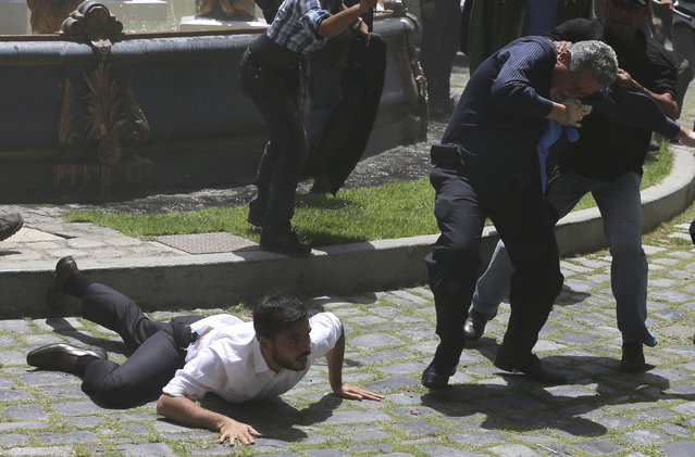 Opposition lawmaker Armando Armas plays possum as fellow legislator Americo De Grazia is slugged by a member of a pro-government militia member during an attack on opposition lawmakers and assembly employees in Caracas, Venezuela, Wednesday, July 5, 2017. Several lawmakers were injured in the attack. De Grazia was taken in a stretcher to an ambulance suffering from convulsions, said a fellow lawmaker. (Photo by Fernando Llano/AP Photo)