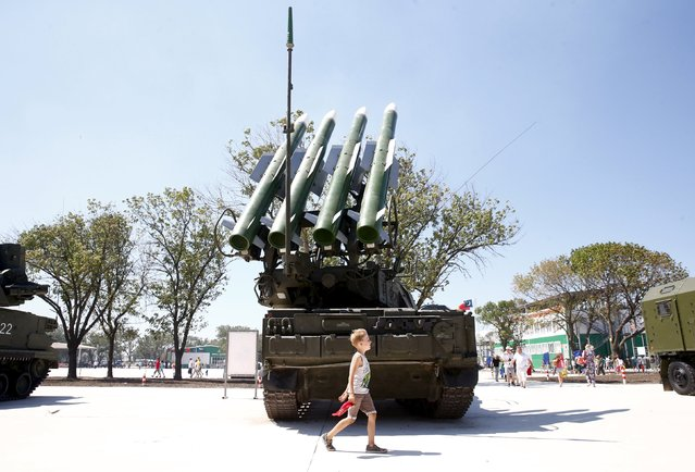 A boy walks past the Russian Buk-1M missile system at the Air defense battle masters competition as part of the International Army Games 2015 in the port town of Yeysk, Russia, August 9, 2015. (Photo by Maxim Zmeyev/Reuters)