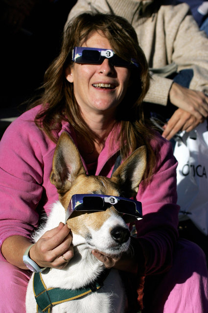 A dog and its owner watch the annular eclipse of the sun in Madrid, October 3, 2005. In an annular eclipse, the Moon moves between the Sun and Earth but, because of a tiny difference in distance due to celestial mechanics, does not completely cover the solar face as in a total eclipse. (Photo by Philippe Desmazes/AFP Photo)