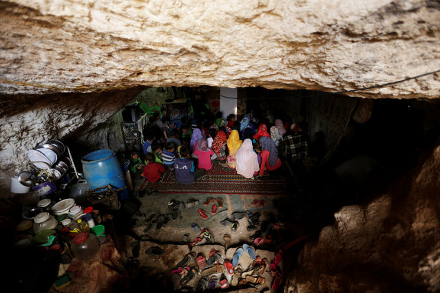 Internally displaced children attend a class inside a cave in the rebel-controlled village of Tramla, in Idlib province, Syria March 27, 2016. A group of people, who live in a cave, have set up a school for children during the day. The cave accommodates around 120 students, divided into two shifts. (Photo by Khalil Ashawi/Reuters)