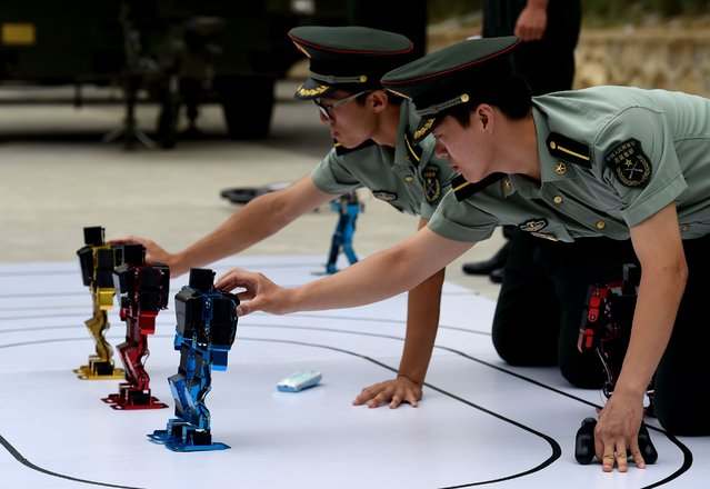 Chinese People's Liberation Army cadets adjust dancing humanoid robots at the PLA's Armoured Forces Engineering Academy in Beijing on July 22, 2014. China's military opened up its engineering academy to journalists on July 22, with demonstrations of rolling tanks, bayonet drills and dancing robots. (Photo by Greg Baker/AFP Photo)