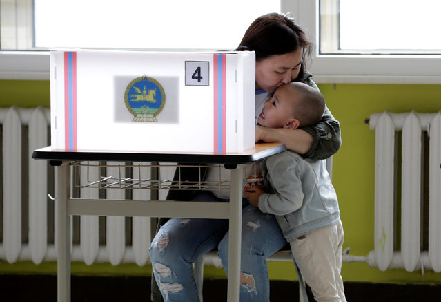 A mother kisses her son as she attends voting for the parliamentary elections at a polling station in Ulaanbaatar, Mongolia, June 29, 2016. (Photo by Jason Lee/Reuters)