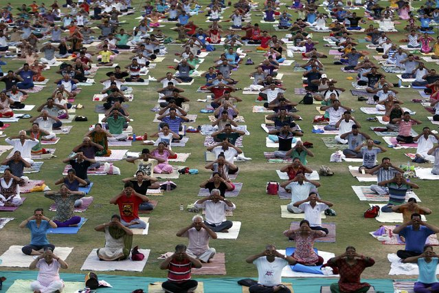 People perform yoga inside a stadium in Ahmedabad, India, June 28, 2016. (Photo by Amit Dave/Reuters)