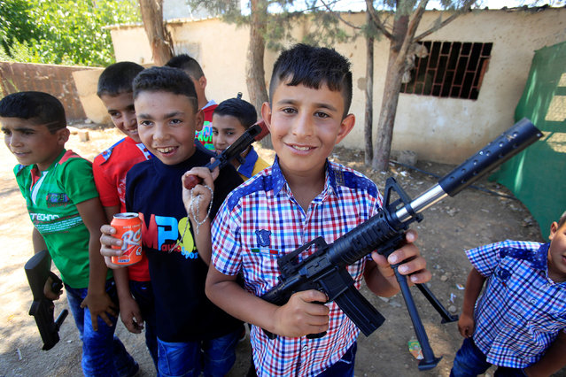 Syrian boys living in the refugee camp of Delhemiyeh village, hold their toy guns as they celebrate Eid al-Fitr, near Zahleh town in the Bekaa valley in eastern Lebanon July 6, 2016. (Photo by Jamal Saidi/Reuters)